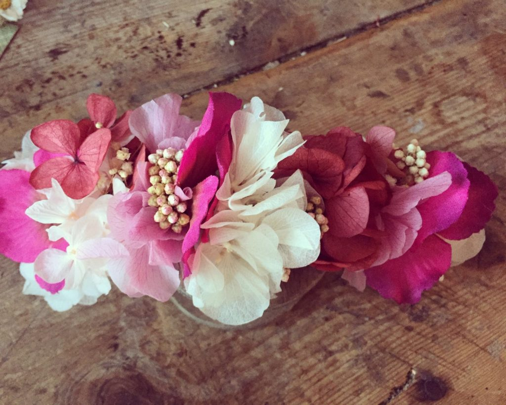 Tocado back en flor preservada en tonos rosas